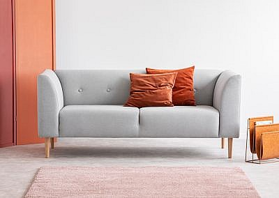 Orange pillows on grey sofa in grey living room interior with pink carpet and screen. Real photo